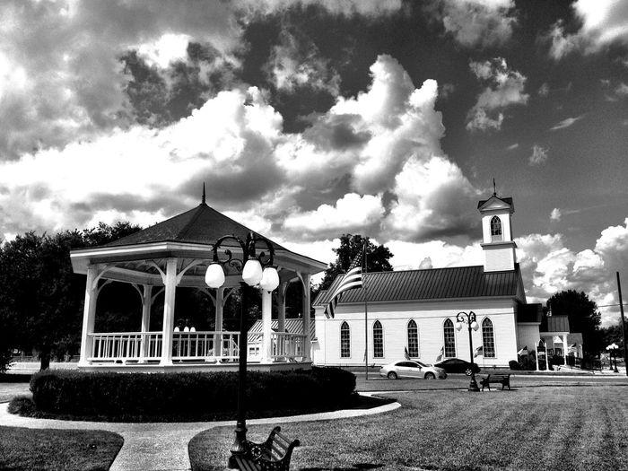 Architecture Built Structure Building Exterior Cloud Sky Façade Arch Day Lawn Outdoors Cloud - Sky Place Of Worship Cloudy Architectural Column Arched City Life No People Band Stand Small Town USA Idyllic Church Texas Traditional Flag