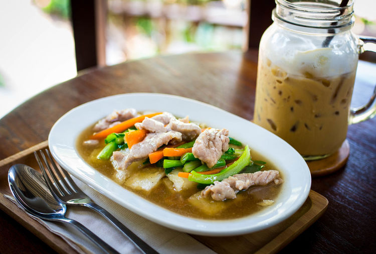 Thai noodle with ice coffee in the background Close-up Day Drink Focus On Foreground Food Food And Drink Fork Freshness Healthy Eating Ice Coffee Indoors  Light And Shadow No People Noodle Plate Ready-to-eat Spoon Table Thai Food Wooden Desk