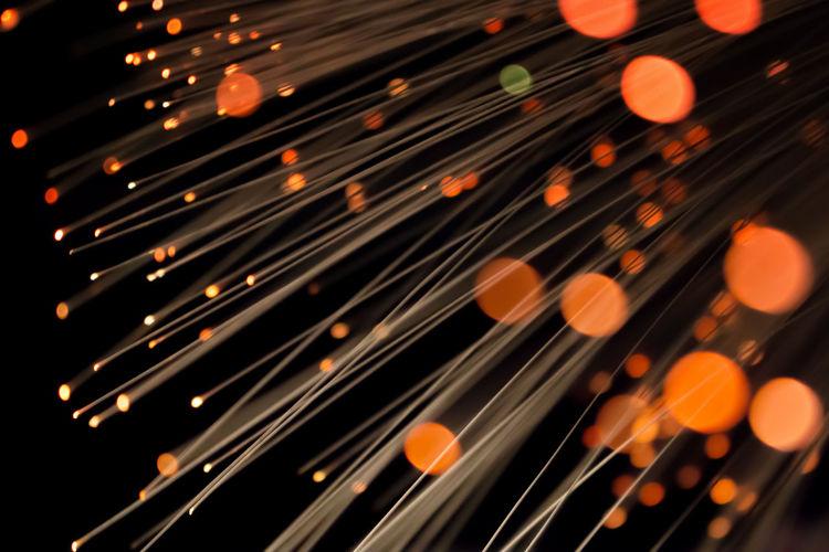 Close-Up Of Illuminated Fiber Optic Against Black Background