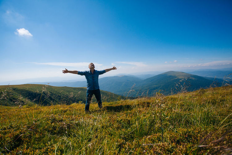Man with arms outstretched on field against sky