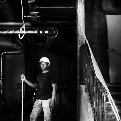 Full length portrait of young man standing in corridor