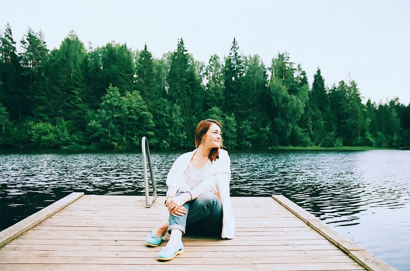Woman Looking At View While Sitting On Pier Over Lake
