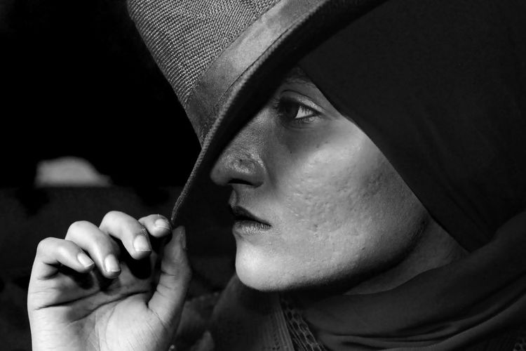 Close-up of woman with hat looking away