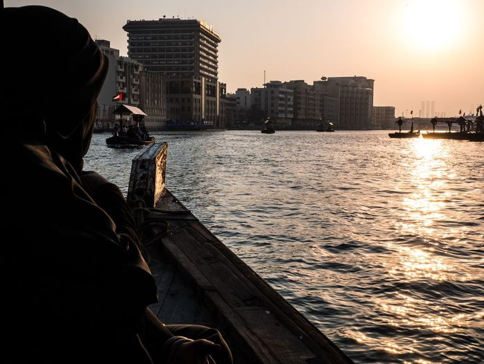Rear view of man on boat in city at sunset