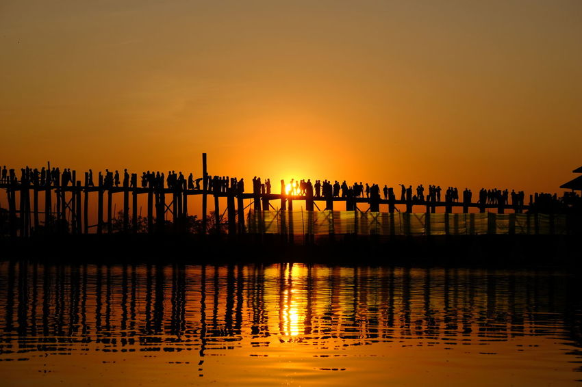 During evening at Ubein Bridge. There will be crowded to see a beautiful sunset on the bridge. Wooden Bridge Beauty In Nature Orange Color Outdoors Silhouette Sunset Ubeinbridge Water