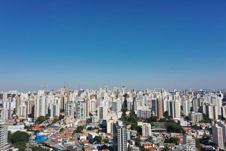 Aerial view of buildings in city against blue sky