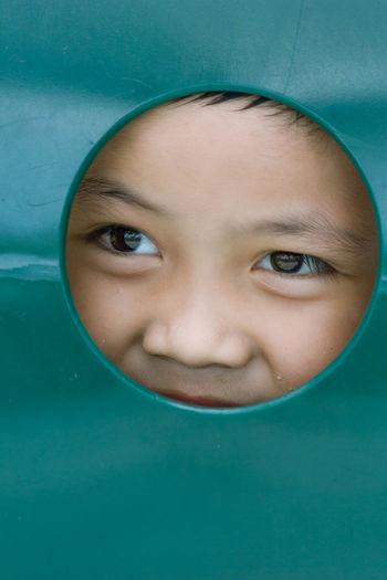 Close-up of boy peeking through circle shape
