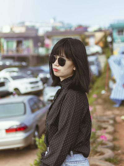 Side view of young woman wearing sunglasses while standing in city