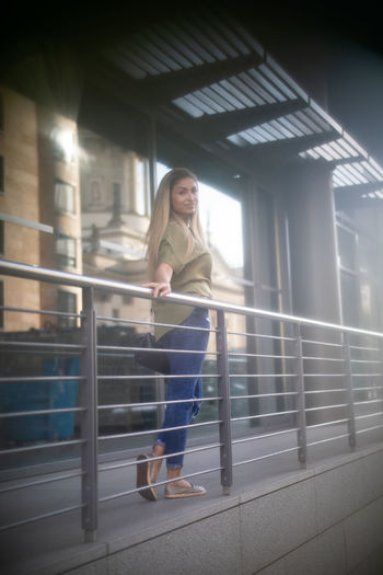 Portrait of woman walking by railing