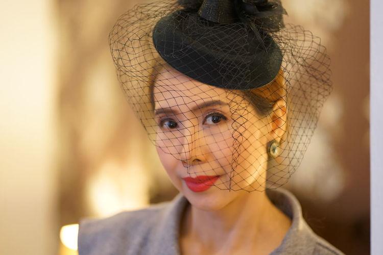 Portrait of woman wearing veiled hat
