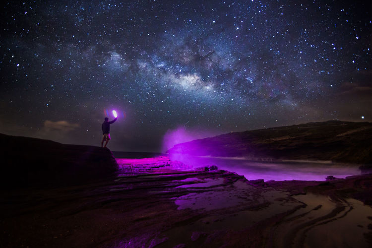 Man standing on beach against sky at night