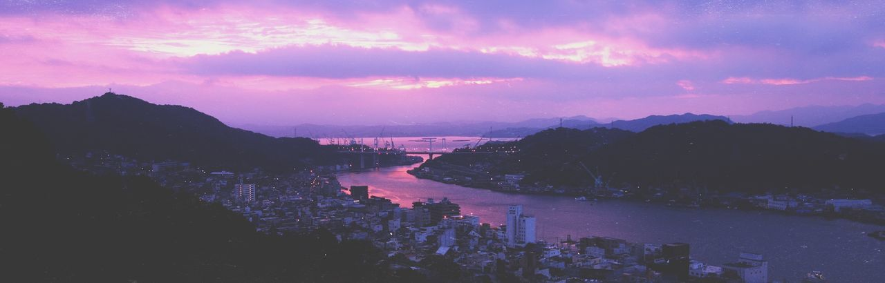River Amidst City Against Sky At Sunset