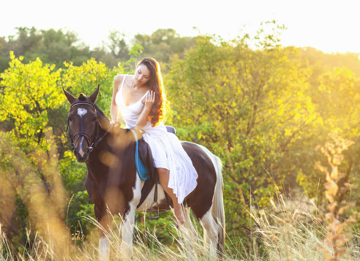 Full length of a young woman riding horse on field
