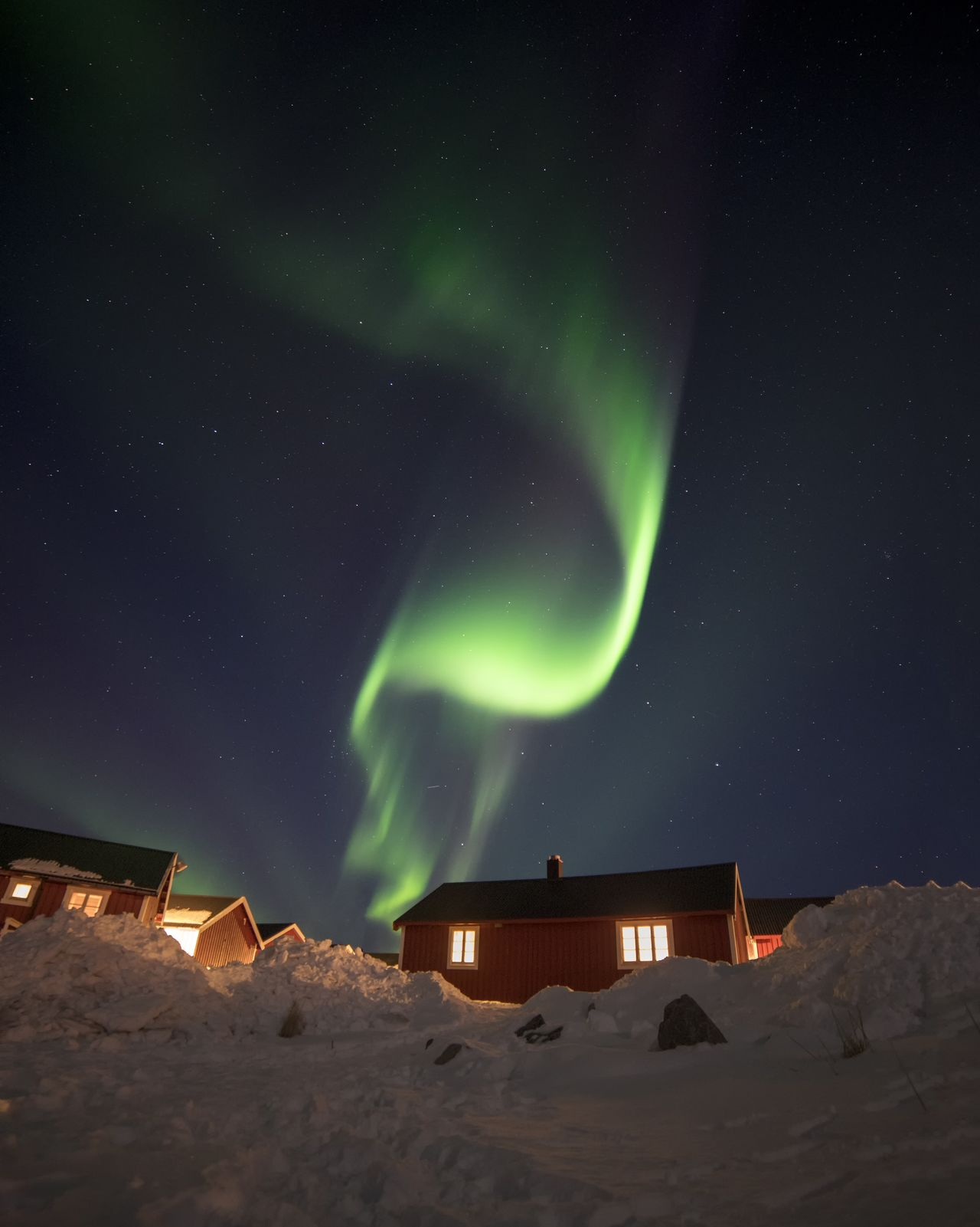 Aurora polaris over houses against sky at night
