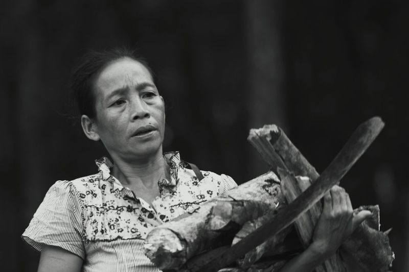 Close-up of mature woman carrying firewood
