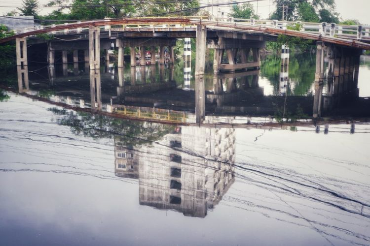 Reflection of abandoned building on snow covered bridge