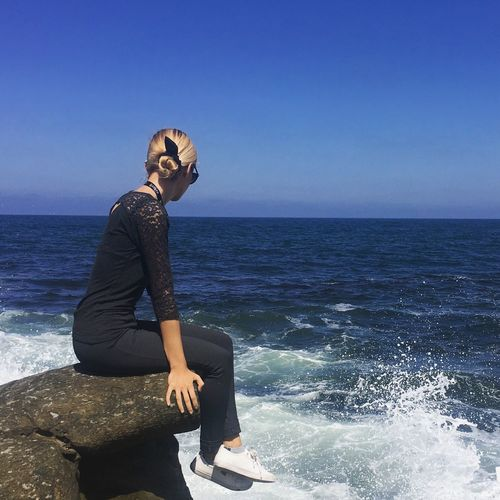 Side View Of Beautiful Woman Sitting On Cliff By Pacific Ocean Against Clear Blue Sky
