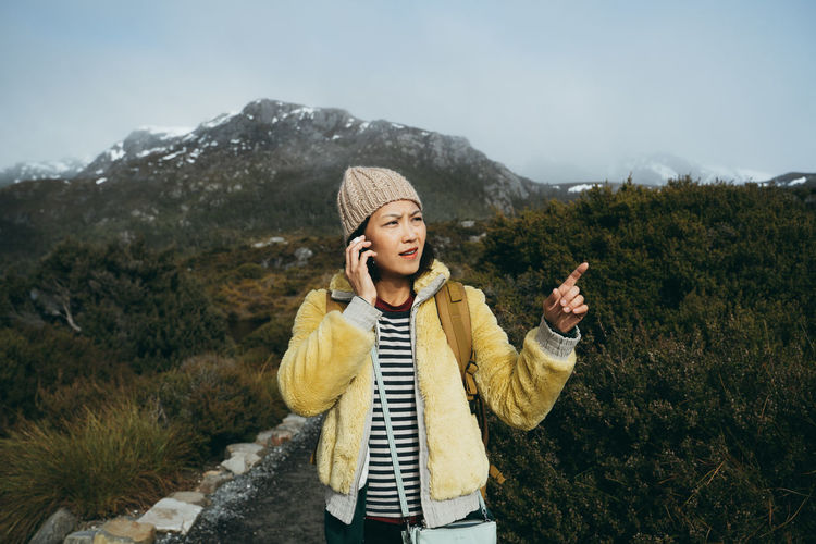 Woman talking over smart phone while standing on mountain against sky