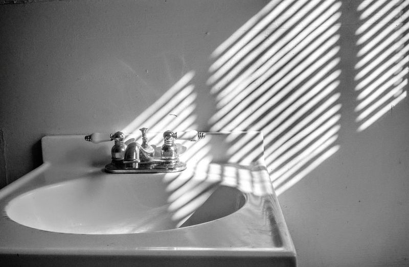 Sunlight on wall by sink in bathroom