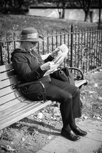 Autumn Hat Park Bench Black And White Break Cap Casual Clothing Day Documentary Full Length Holding Leaves Lifestyles Lunch Time Newspaper One Person Outdoors Real People Senior Woman Sitting