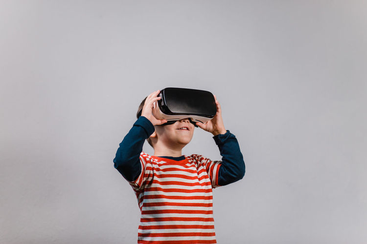 Excited kid having fun with VR glasses. Portrait of cheerful child wearing virtual reality headset against grey background. Child Front View Striped Mouth Open One Person Indoors  Vr Virtual Reality Portrait Boy Red Color Headset Glasses Caucasian Technology Preschool Isolated Gadget Digital E-learning 3D Horizontal Education Hands Spread Having Fun