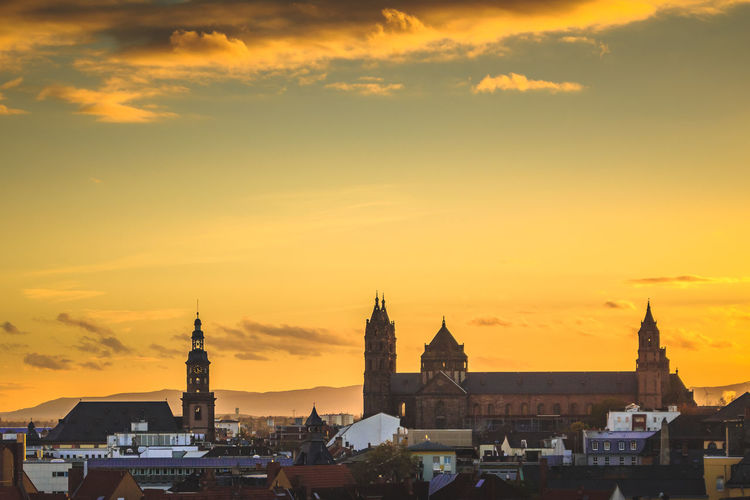 Wormser dom by buildings against sky during sunset