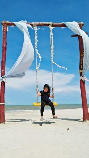 Full length of girl on swing at beach