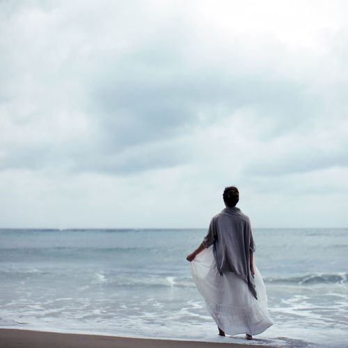 Rear View Of Woman Standing At Sea Shore Against Sky
