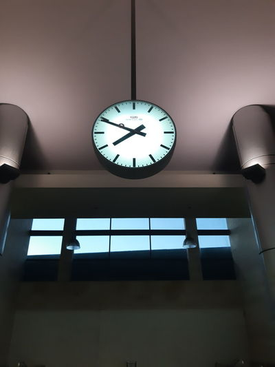 Low angle view of illuminated clock hanging on ceiling