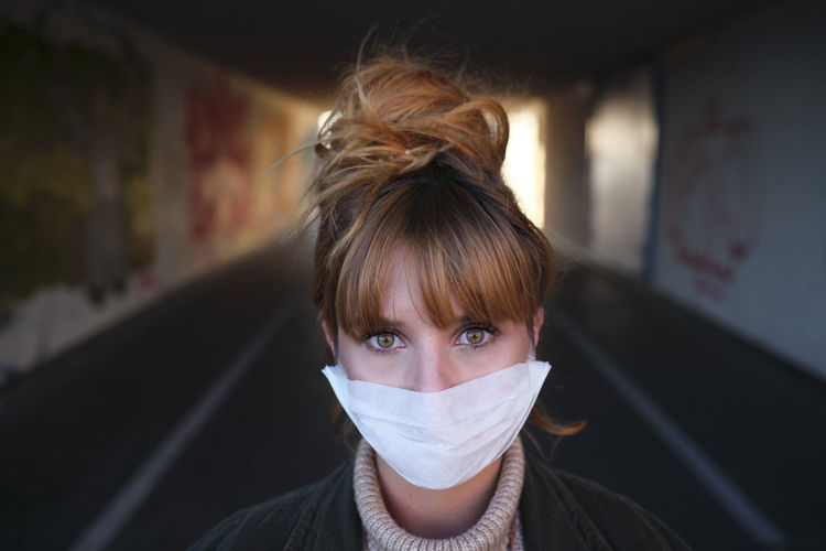 Portrait of woman wearing mask standing in basement
