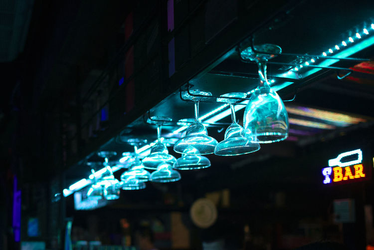 Low angle view of illuminated glasses hanging in bar at night