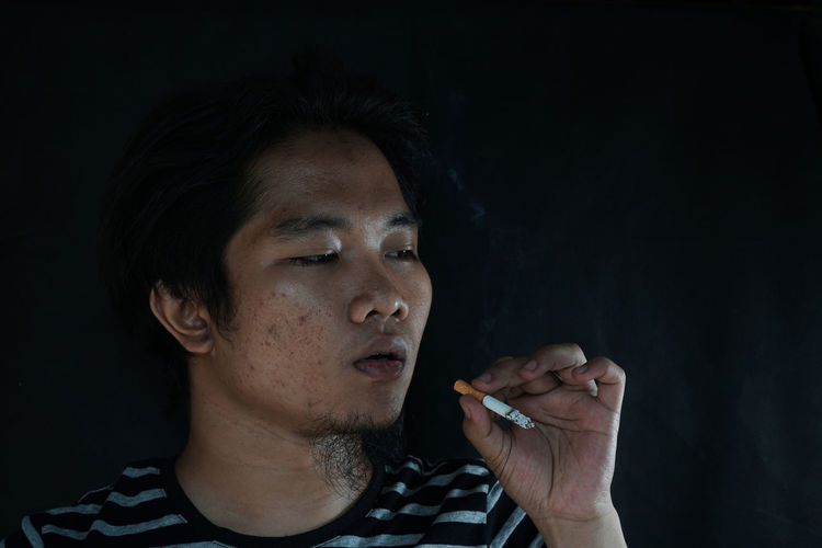 Portrait of a man smoking cigarette isolated on black background. Addiction Adult Adults Only Bad Habit Black Background Cigarette  Close-up Day Headshot Indoors  Marijuana - Herbal Cannabis Men One Man Only One Person Only Men People Real People RISK Smoke - Physical Structure Smoking - Activity Smoking Issues Social Issues Studio Shot Young Adult
