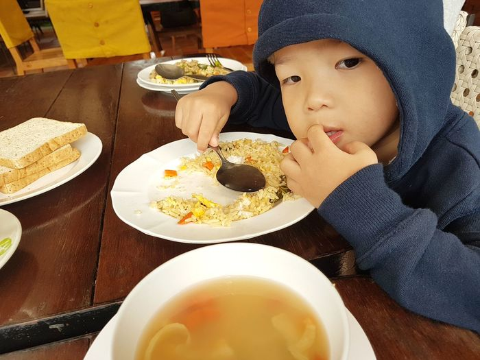 Close-up of cute boy wearing hooded shirt having meal at home