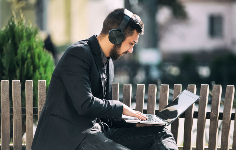 Side view of businessman using laptop while listening music on bench