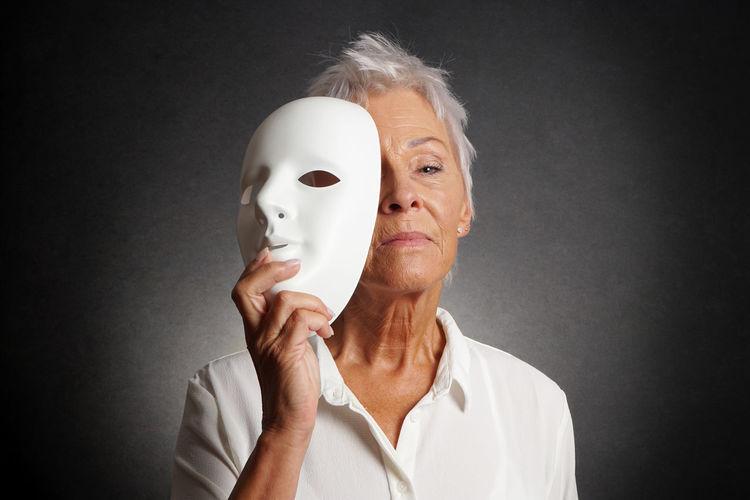 Senior woman wearing mask against black background
