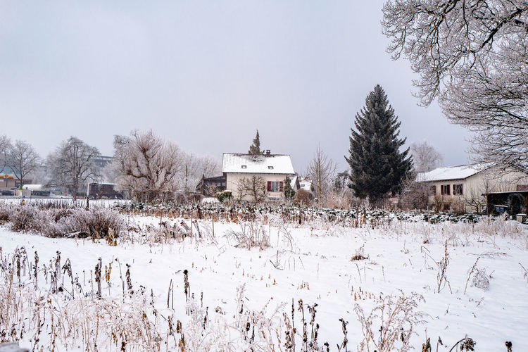 Houses on snow covered field against sky