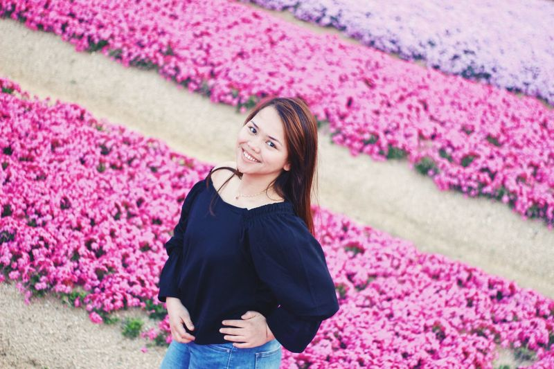 Portrait of smiling young woman standing on pink flowers