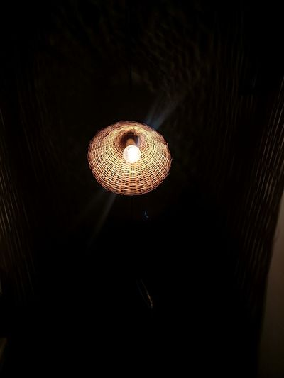 Low angle view of illuminated pendant light in the dark