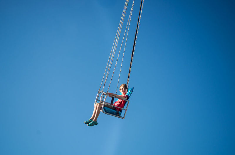 Boy dreams of flying while sitting on a Chain Carrousel Adventure Blue Botany Carroussel Childhood Clear Sky Copy Space Day Full Length Fun Hanging Leisure Activity Mid-air Motion One Person Outdoors Real People Sky