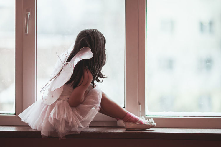 Girl wearing costume looking through window at home