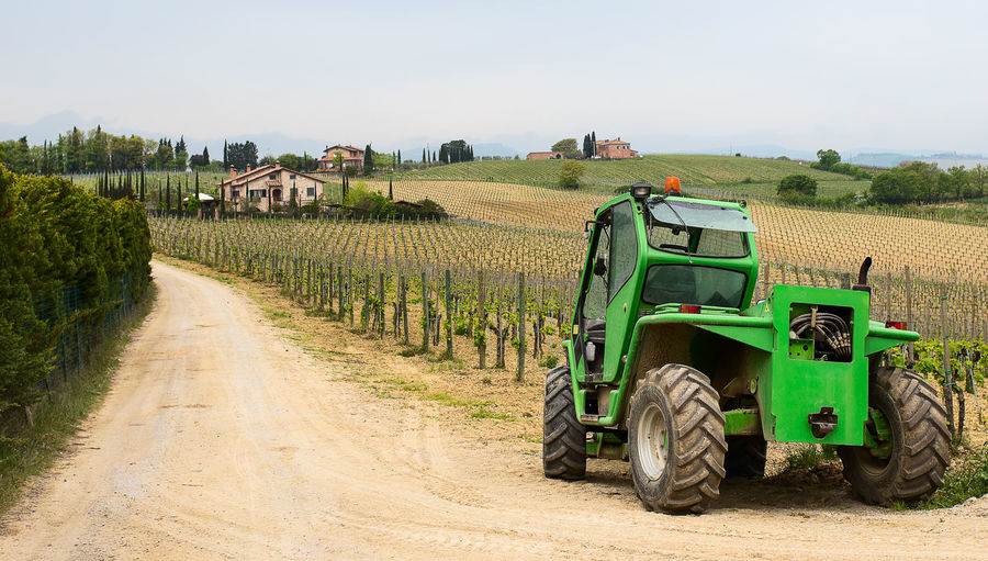 Tractor of dirt road against farm