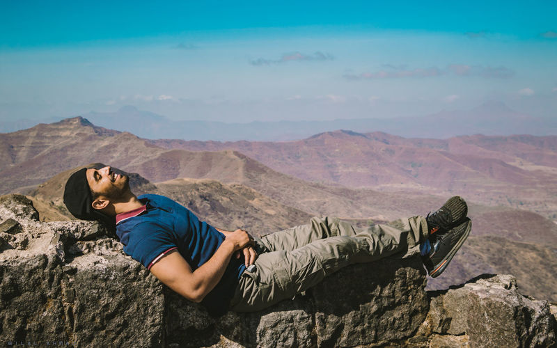 Side view of man lying on mountain against sky