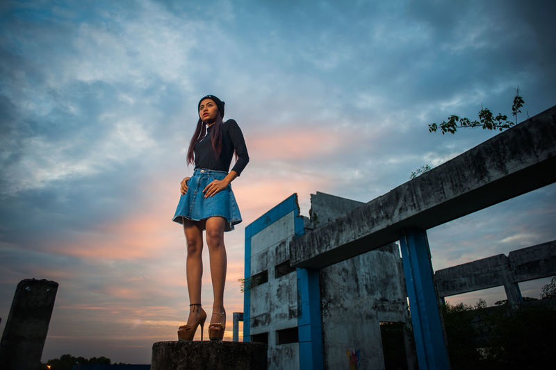 Low angle view of young woman against abandoned building during sunset