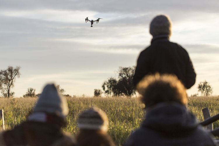 Rear view of people on field with drone flying against cloudy sky