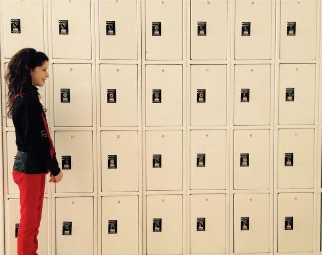 Side view of teenage girl standing against lockers