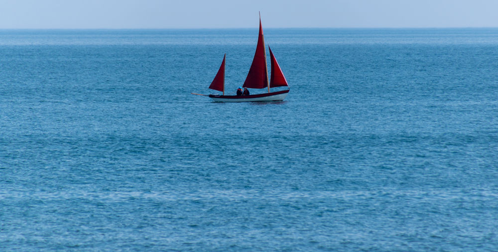 Closer in on the yawl rigged craft Red Beauty In Nature Blue Day Horizon Horizon Over Water Idyllic Luxury Mode Of Transportation Nature Nautical Vessel No People Outdoors Sailboat Sailing Scenics - Nature Sea Sky Tranquil Scene Tranquility Transportation Water Waterfront Yawl