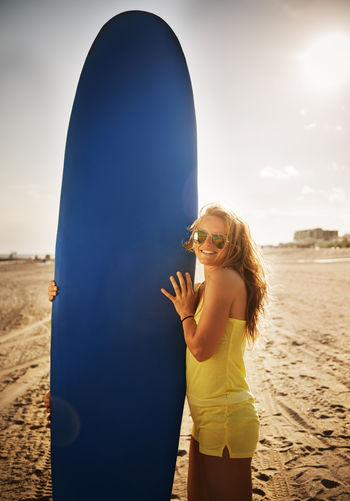 Woman with surfboard standing at beach against sky