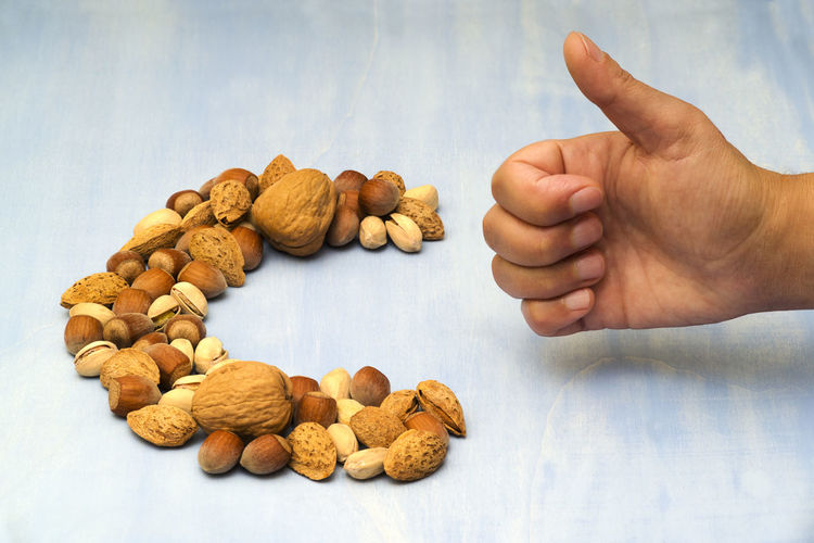 Cropped hand of man gesturing thumbs up with dried fruits on table