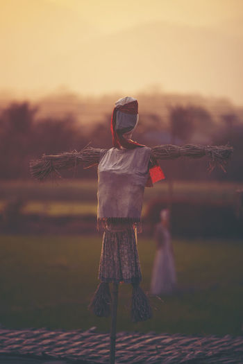 Scarecrow on field during sunset
