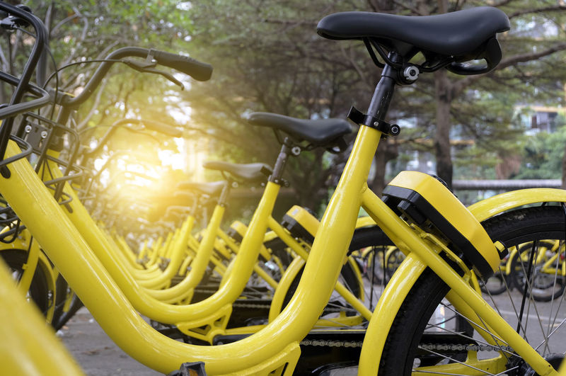 Rows of bright yellow public rental bikes on a street. Bicycle Bicycle Rack Close-up Day Land Vehicle Mode Of Transport No People Outdoors Spoke Stationary Transportation Wheel Yellow